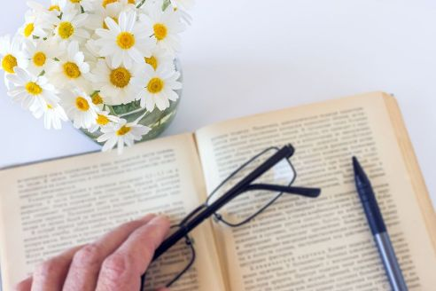 bigstock-Glasses-In-Hand-On-An-Old-Book-240896221