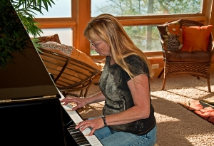 Older Woman Playing Piano In Sunlit Home
