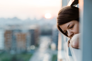Young Sad Woman Looking Outside Through Balcony Of An Apartment